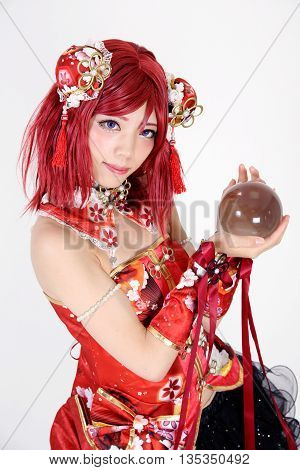 Young asian girl dressed in cosplay costume with crystal ball on white background