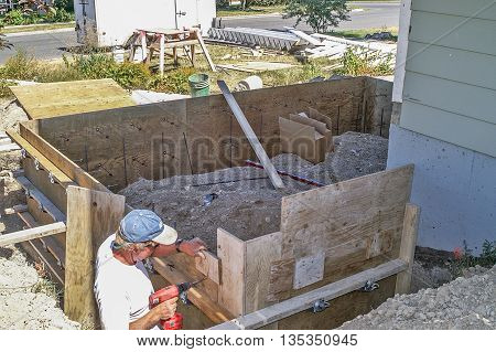 Construction worker building plywood forms to hold the cement for the footings for a home addition