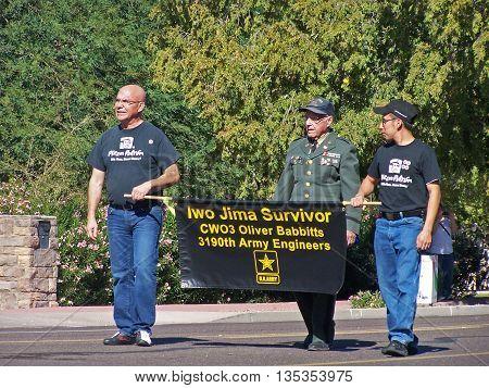 PHOENIX, AZ- NOV. 11: Iwo Jima Survivor walking with two escorts holding banner in Veteran's Day Parade in Phoenix, AZ on November 11, 2013.