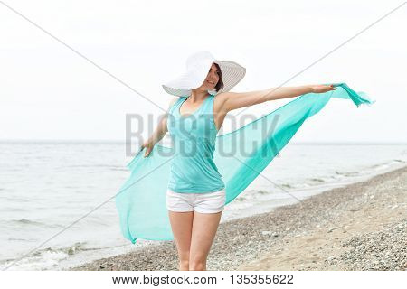 Portrait of a beautiful woman with a turquoise scarf and a big white hat on the beach enjoying the summer. Jumping on the beach. Travel and Leisure. Freedom Concept.