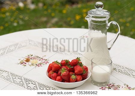 Bowl of strawberries standing on the table with glass of milk. Jug full of milk beside bowl of strawberries. Summer breakfast. Summer desert. Picnic idea. Healthy option