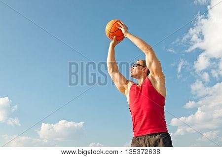 muscular guy plays basketball alone in the red shirt and black shorts