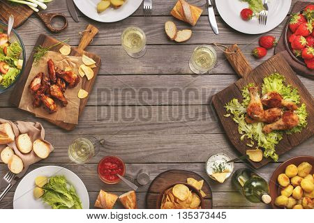Outdoors Food Concept. On the wooden table different food with copy space grilled chicken legs buffalo wings bread salad potatoes strawberry and wine glasses with wine bottle