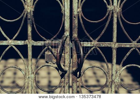 Old aged rusty metal fence with doorknobs and lock outdoor on dark background
