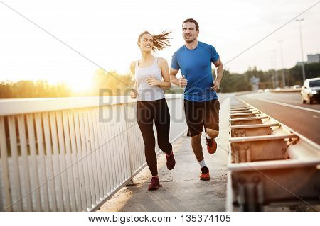 Active young couple jogging outdoors during sunset