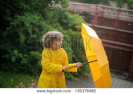 The boy in a bright yellow raincoat opens an umbrella standing under a rain. The child is in the yard of the house. Drops of a rain fall to it on the head. The boy with a cheerful laughter opens a yellow umbrella.