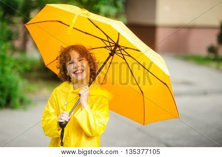 The cheerful boy under a yellow umbrella. The child with a smile looks in the camera having squinted. It has wild curly hair and a nice face. The boy is dressed in a bright yellow raincoat.