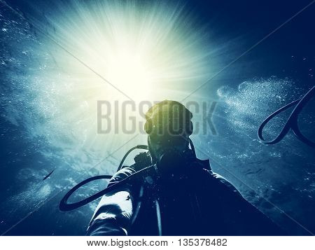 Man doing scuba diving in the ocean with sunbeam in the background entering into the water.