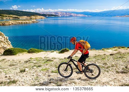 Mountain biker riding on bike in summer inspirational mountains and sea landscape view. Man cycling MTB on enduro dirt and rocky trail track. Sport fitness motivation and inspiration outdoors. poster