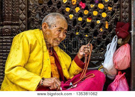 KATHMANDU, NEPAL - CIRCA MARCH 2013: Elderly Buddhist nun holding her prayer beads at Boudhanath stupa.