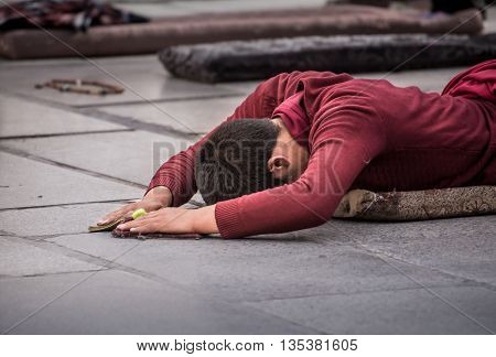 A nun performing prostration in front of a monastery