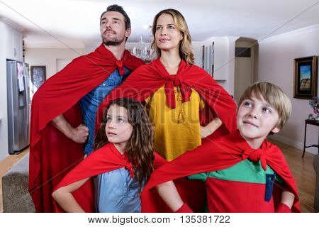 Family pretending to be superhero in living room at home