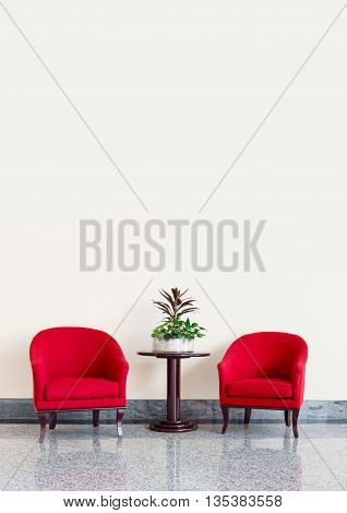 Red armchairs against a neutral wall background with copyspace