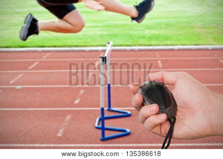 Composite image of coach is holding a stopwatch against assertive male athlete jumping above hedge during a race