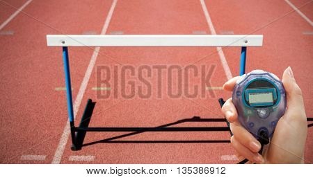 Close up of woman is holding a stopwatch against focus of hurdle on athletics field