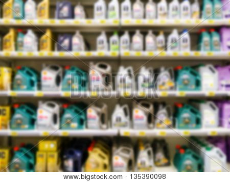 Blurred colorful motor oil bottles on shelves in supermarket as background