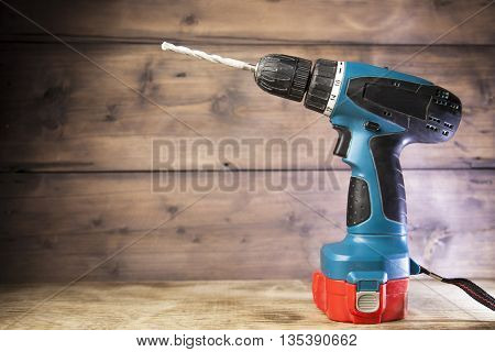 electric drill on a wooden background,drill blue,red