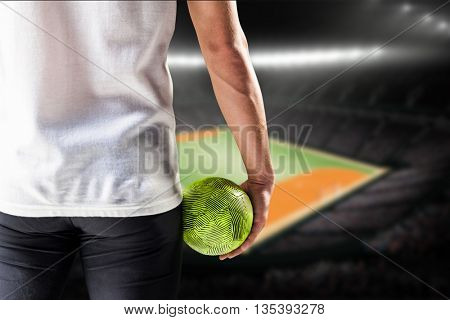 Mid section of athlete man holding ball against handball field indoor
