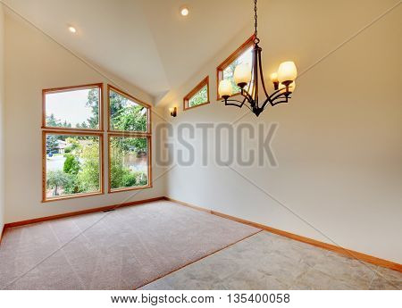 Empty Room Interior In Beige Tones With Large Window And Vaulted Ceiling.
