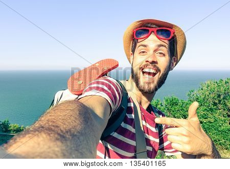 Young man taking travel selfie on trekking excursion day - Hipster guy self photo at view point with blue ocean background - Concept of healthy lifestyle in beauty of nature - Soft vintage filter look