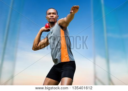 Front view of sportsman practising shot put against scenic view of blue sky