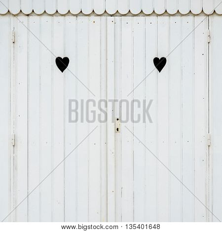Detail of white wooden beach hut with two carved hearts in the doors.