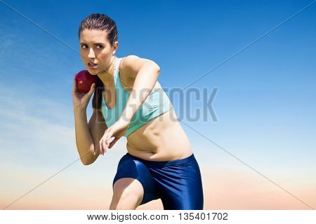 Sportswoman practising the shot put against scenic view of blue sky