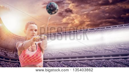 Sportswoman throwing a hammer against composite image of stadium