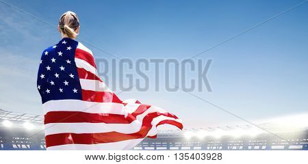 Rear view of sporty woman holding an American flag against large football stadium under bright blue sky