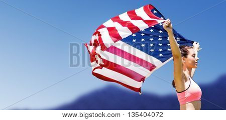 Profile view of sportswoman raising an american flag against scenic view of blue sky