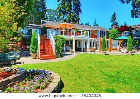 Large Orange House With White Trim. View Of Back Yard With Patio Area.