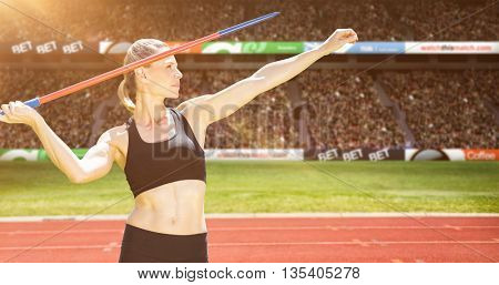 Front view of sportswoman practising javelin throw against view of a stadium