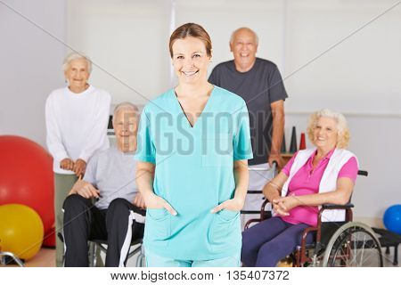 Smiling geriatric nurse standing in front of a happy group of senior people
