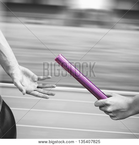Athlete passing a baton to the partner