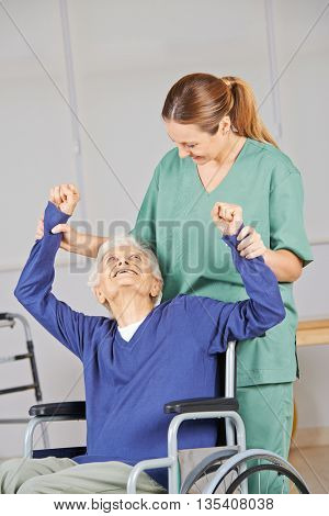 Old woman doing physiotherapy in nursing home with geriatric nurse