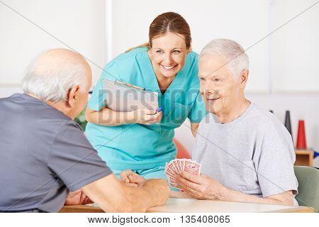 Smiling geriatric nurse watching twi old men playying cards in a nursing home