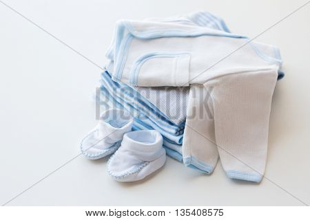 clothing, babyhood, motherhood and object concept - close up of white baby cardigan with bootees and pile of clothes for newborn boy