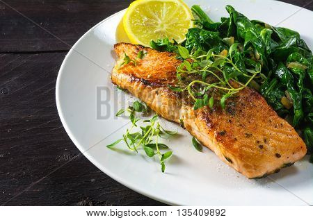 grilled salmon with thyme lemon and spinach on a white plate on a dark rustic wooden table homemade vegetarian low carb dish close up with selected focus narrow depth of field
