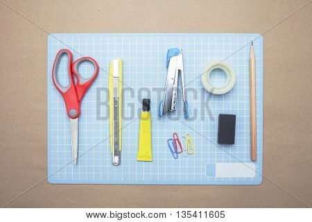 Business concept:stapler,glue,scissor,cutter,tape,pen,pencil,clip,ruler,rubber, cutting mat and color pencil on brown paper background.Top view