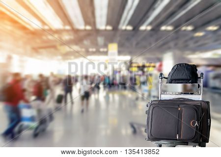 Closeup of the luggage and backpack on a trolley with the blurred of the airport terminal background.