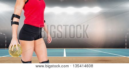 Female athlete with elbow pad holding handball against digital image of handball field indoor