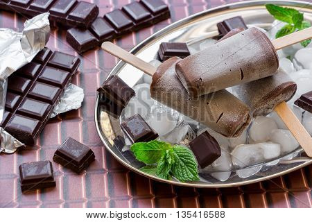 Chocolate ice cream on a stick on a silver platter with ice and pieces of chocolate mint leaves near pieces of chocolate on a chocolate background. Chocolate ice cream popsicles. Horizontal. Close.