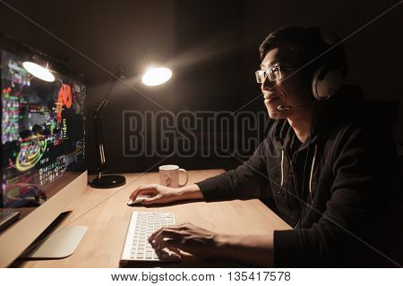 Happy handsome asian male gamer playing computer game at the table in dark room