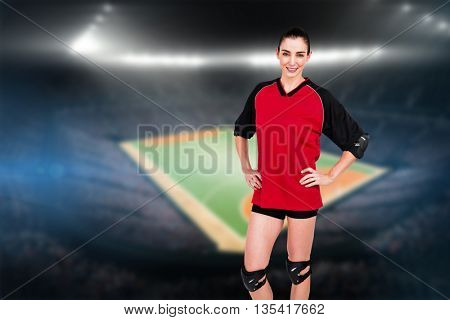 Female athlete posing with elbow pad and knee pad against handball field indoor
