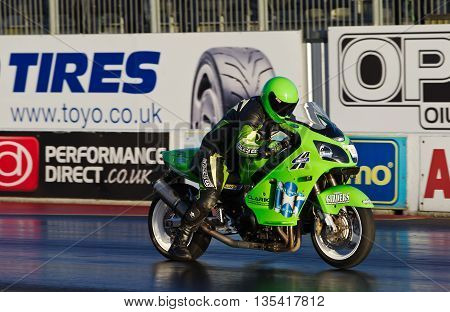 PODINGTON, UK - OCTOBER 19: An unnamed rider takes his modified Kawasaki street bike down the Santa Pod raceway at speed during the Extreme Performance Bike event on October 19, 2014 in Podington