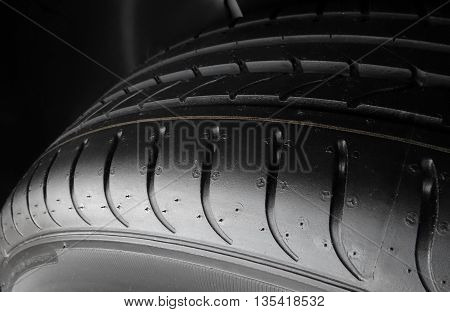 Car parts shop. Tread blocks and grooves on new tire detailed