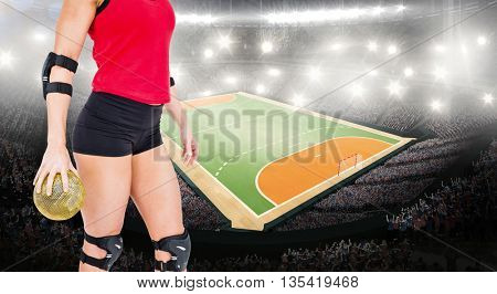 Female athlete with elbow pad holding handball against handball field indoor
