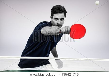 Portrait of male athlete playing table tennis against grey background