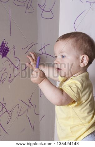 Baby boy drawing with wax crayon on plasterboard wall. He is looking to the crayon