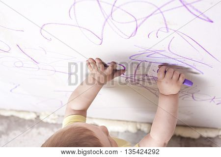 Baby boy drawing with wax crayon on plasterboard wall. High angle view